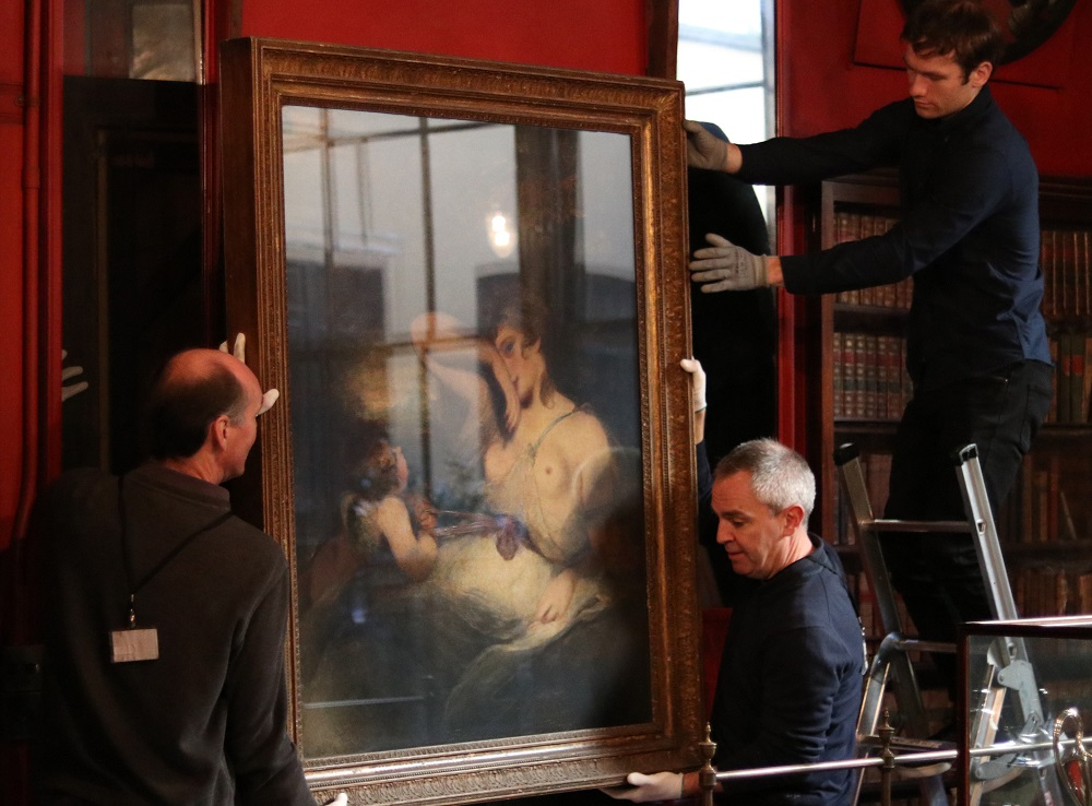 Art handlers carefully remove The Snake in the Grass from its position on the west wall of the Library Dining Room