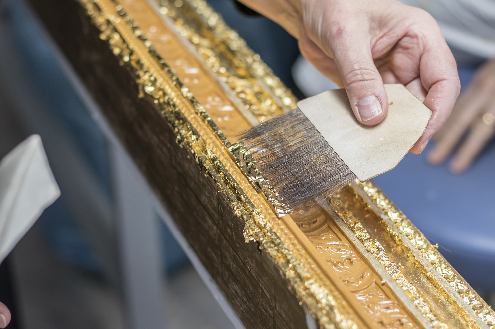 Applying gold leaf to the frame using a squirrel-tail brush