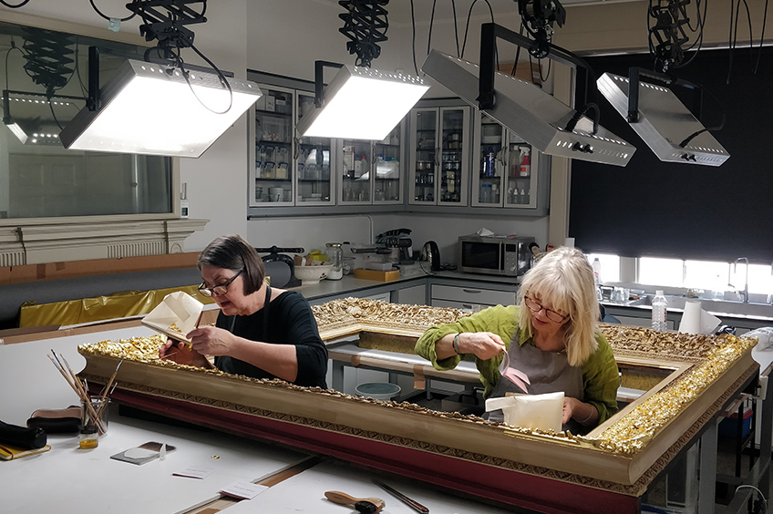 Conservators working on the frame of Sir John Soane's portrait