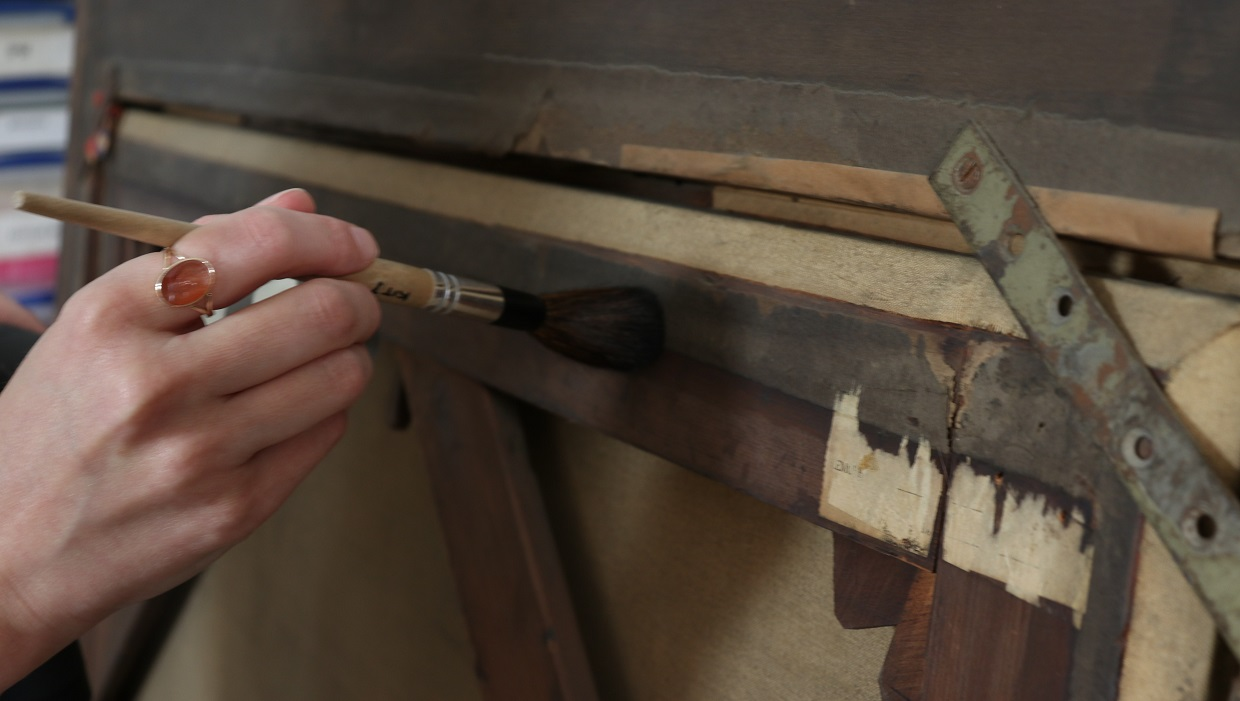 Initial dusting of the back of the canvas following the placement of the work in the conservation studio