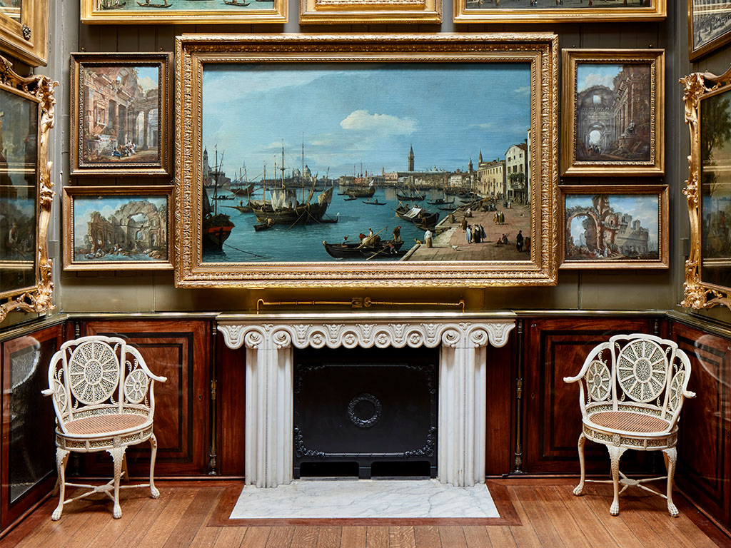 Two of the Picture Room chairs beneath paintings by Canaletto and either side of a fireplace