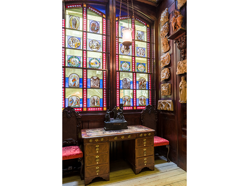 A desk in the Monk's Parlour with a stained glass window behind it and lit candles