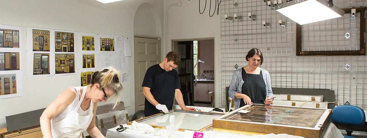 Photograph of our Conservation team working on objects in the new purpose-built conservation studio