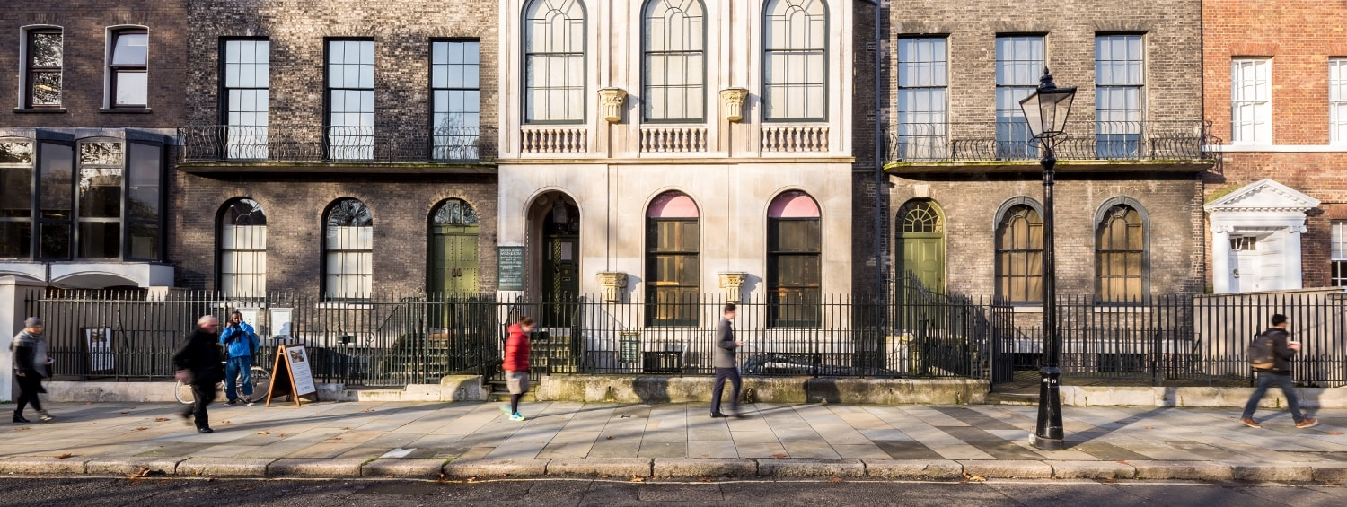 The facade of Sir John Soane's Museum is separated from the street by a series of boundaries, including iron railings and a basement area