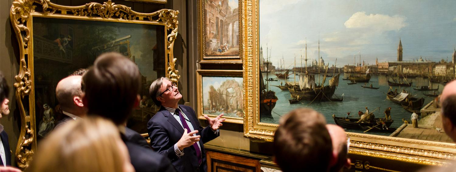 Photograph of a curator leading a tour in the Picture Room looking at works by Canaletto