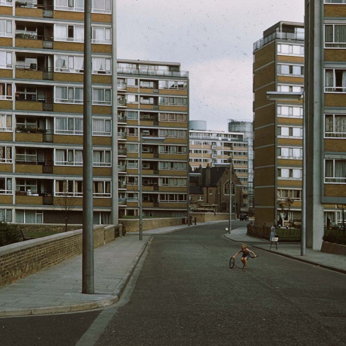 Photograph of tower blocks and a street with a boy playing with a wheel