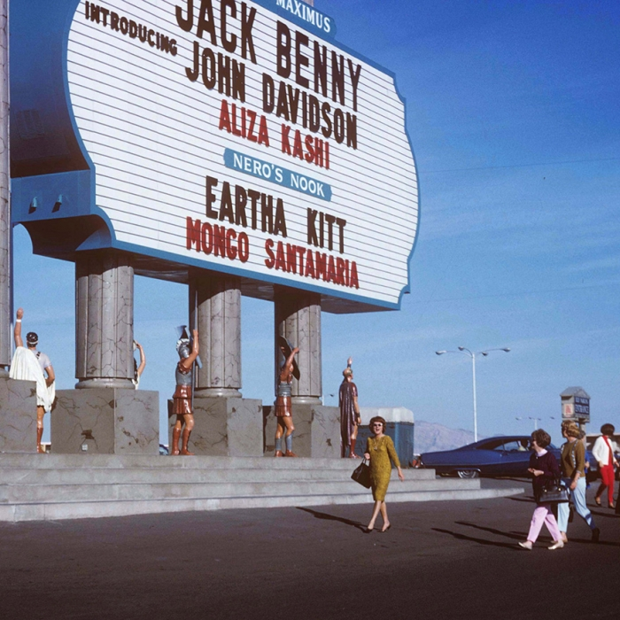 A huge billboard in Las Vegas with people stood around in Roman outfits
