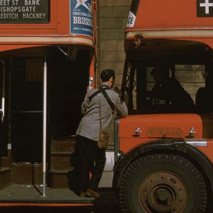 Two red London buses with a ticket inspector and bus driver talking