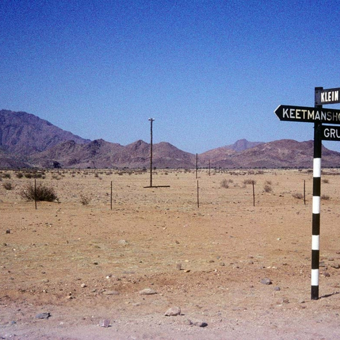 Photograph of a signpost, fencing and telegraph posts in a desert