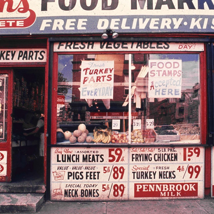 A Grocery shop with lots of signs on its front