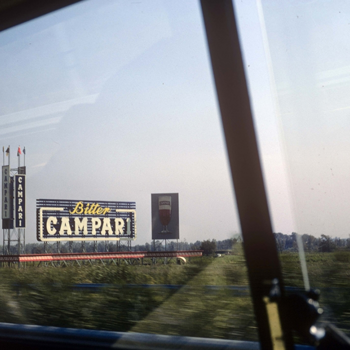 Photo taken from a car window with a large Campari ad billboard standing in a field by the road