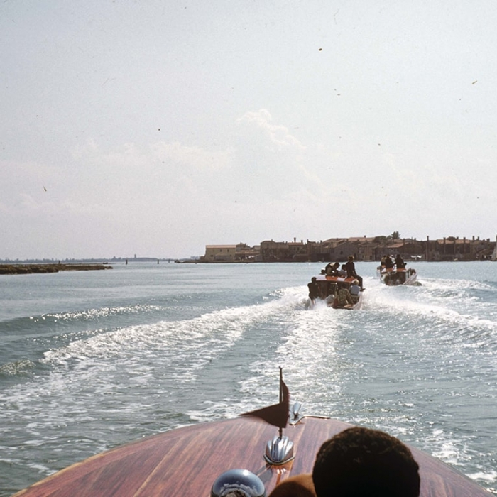 Photo taken from a taxi boat or speedboat in the Venetian lagoon, looking over the bow to more boats ahead and, on the horizon, Venice