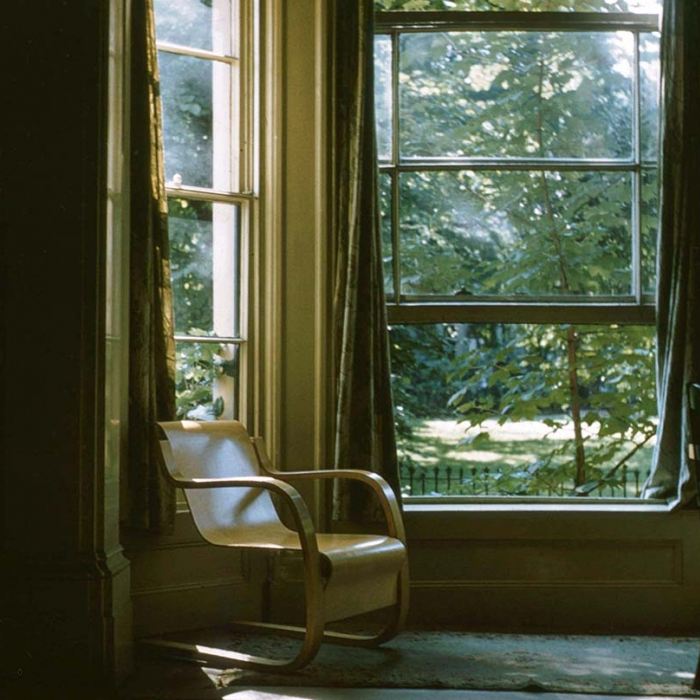Interior of a flat with a chair by a window, through which trees are visible