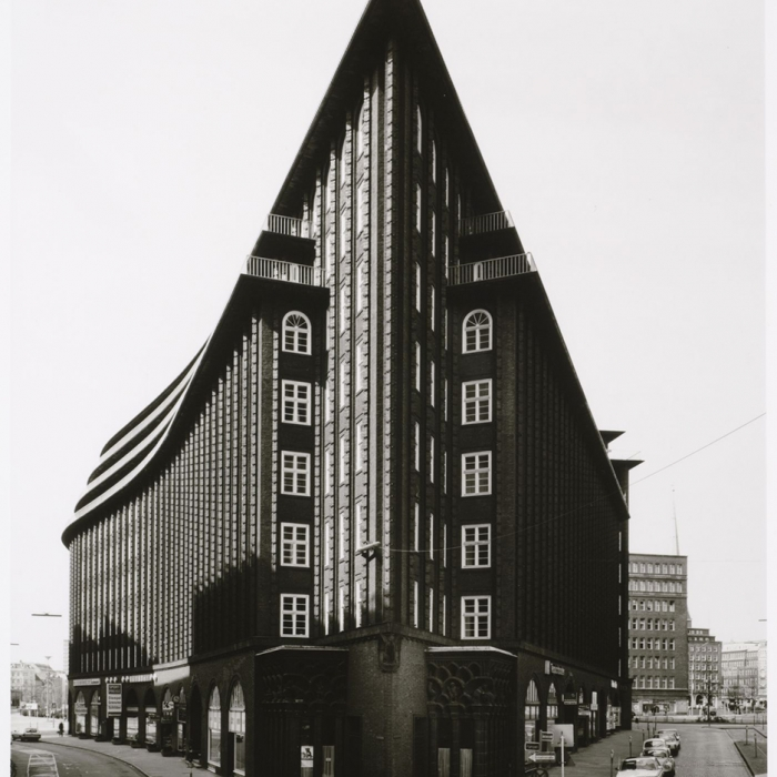 Striking black and white image of a building, with the angle exaggerating the corner, making it seem to cut into the sky