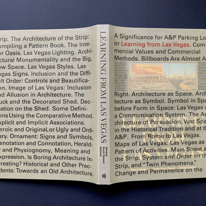 The book Learning from Las Vegas placed opened and face down on a surface so as to show its cover, which is covered with text.