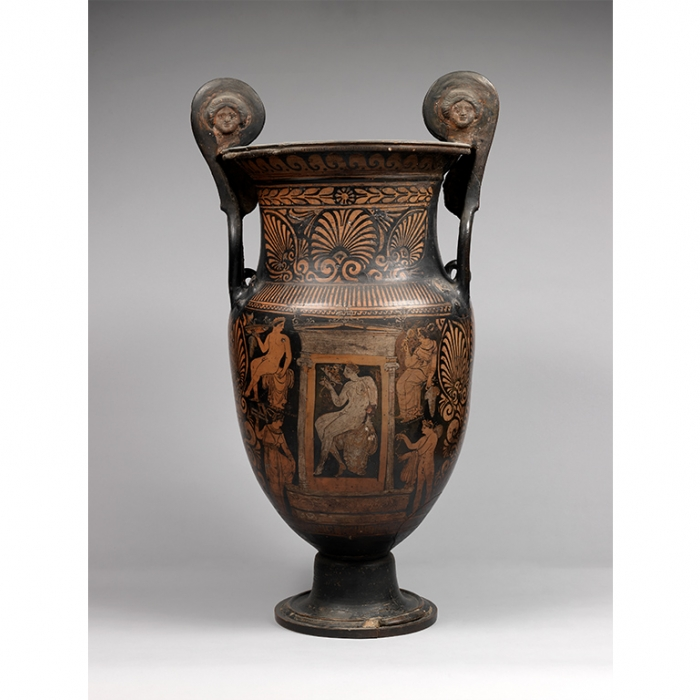 A vase decorated with orange figures upon a dark background, with an image of a seated youth