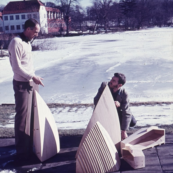 Two men in an outside space discussing a scale study model of Sydney Opera House