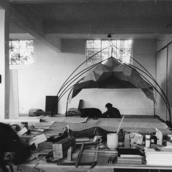 Black and white photo of office with large study model being worked on by an architect