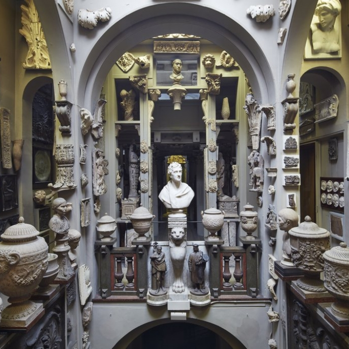 A room filled to the brim with plaster casts from ancient monuments, urns, and statue busts all placed around a central void