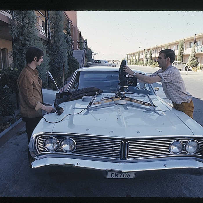 Two people affixing a camera to a car