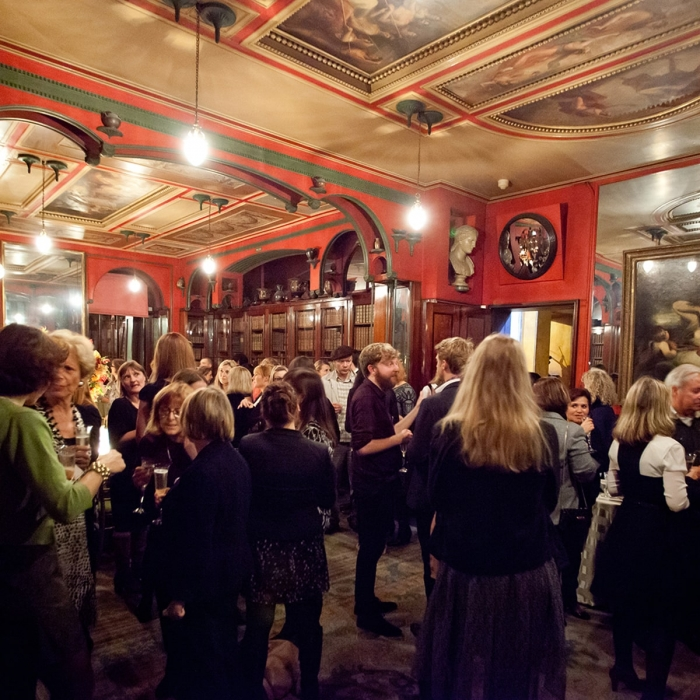 Photograph of a drinks reception in full swing in the Library-Dining Room of Sir John Soane's Museum