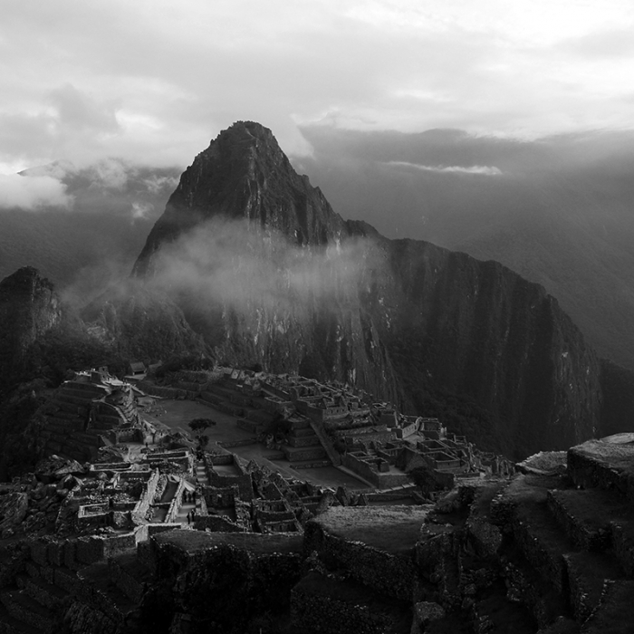 Machu Picchu, with sunlight shining onto the ruins, and clouds floating over the site