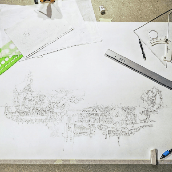 A drawing surrounded by sketches, pencils, rulers