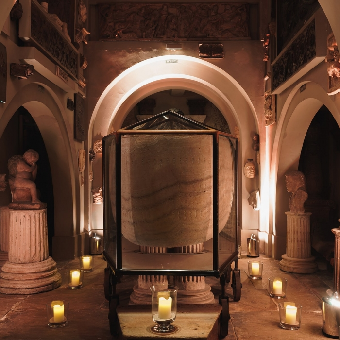 Photograph of the Sarcophagus lit by candlelight and dramatic spotlighting at a Soane event