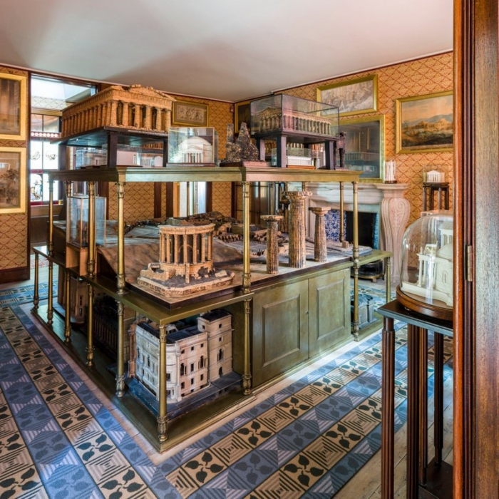 A photo of the Model Room in the Soane Museum which is a smallish room with a central stand containing numerous architectural models on three shelves. It stands about 6 feet high.