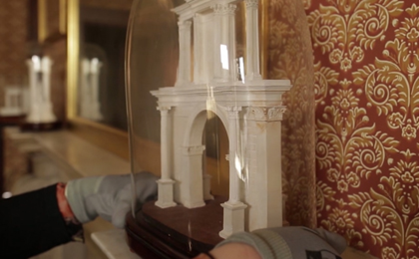 A conservator carefully placing an architectural model by Jean Francois Fouquet on a mantle