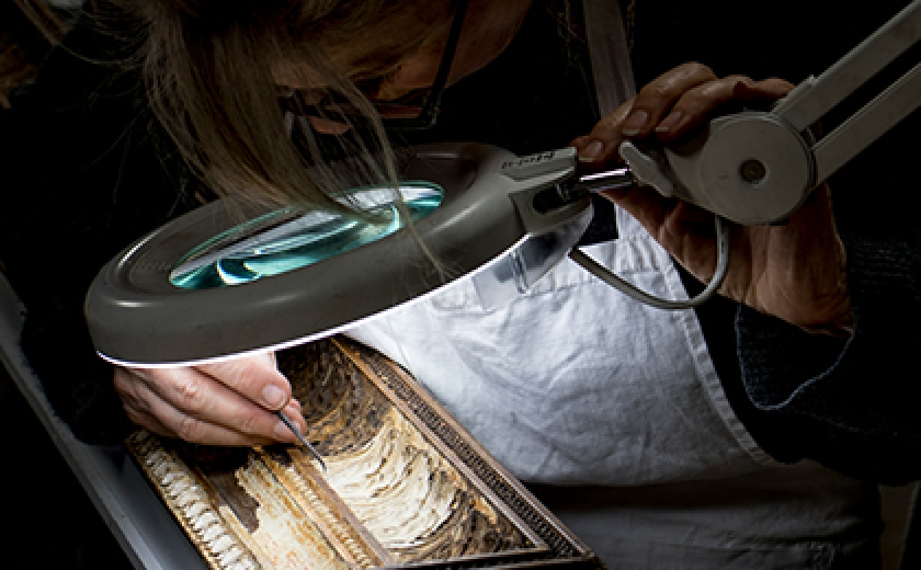 A conservator uses an illuminating magnifying glass to work on the delicate moulded details of the frame of the Snake in the Grass