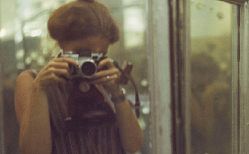 Photograph of Denise Scott Brown taking a photograph of herself in a mirror