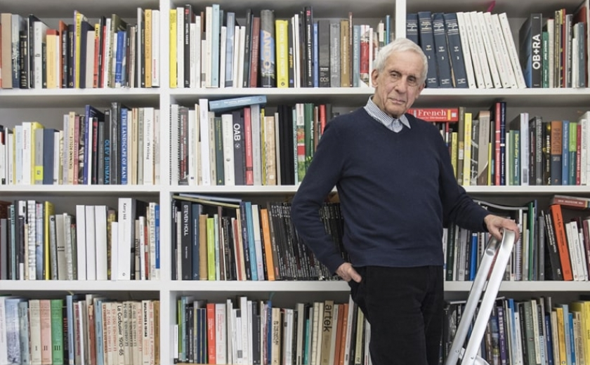 Kenneth Frampton, recipient of the 2019 Soane Medal, standing on a ladder in front of a row of bookshelves
