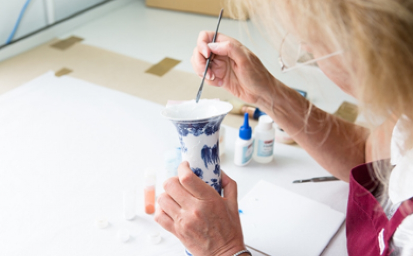 Photograph of a member of the conservation team working on a ceramic item from our collection