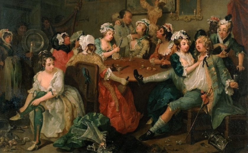 A scene from The Rake's Progress by Hogarth. This oil painting depicts a drunken man in a room full of raucous prostitutes. Two caress him, simultaneously stealing his pocket watch
