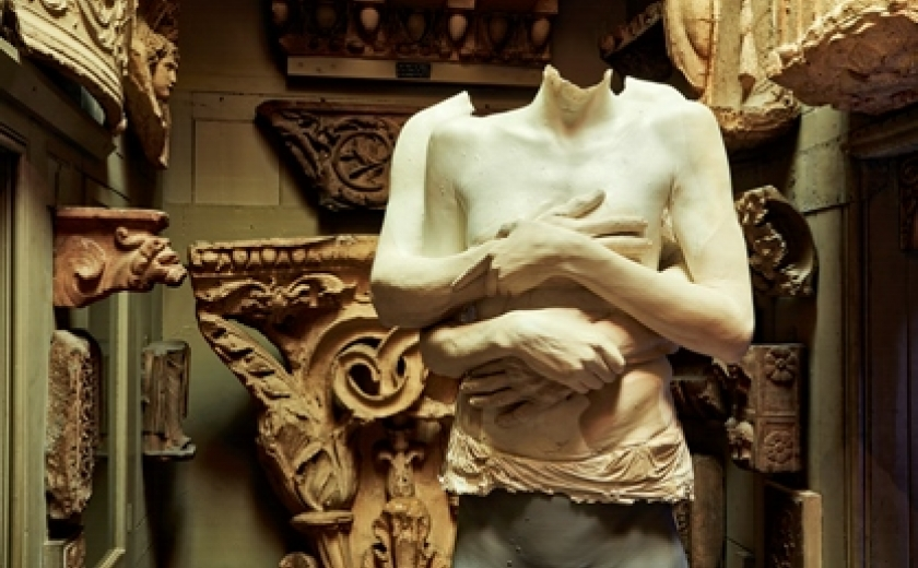 Marc Quinn's sculpture Untrimmed on display at the Soane Museum. This image depicts the work, a sculpture depicting a man and woman embracing, in front of the architectural sculptures of the Museum.