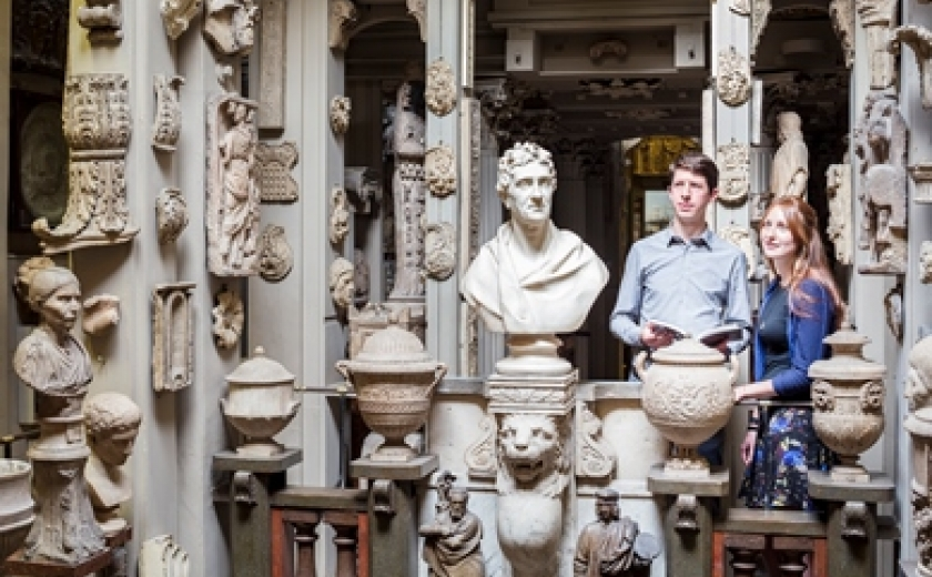 Photograph of two visitors in the Dome Area next to the bust of Soane