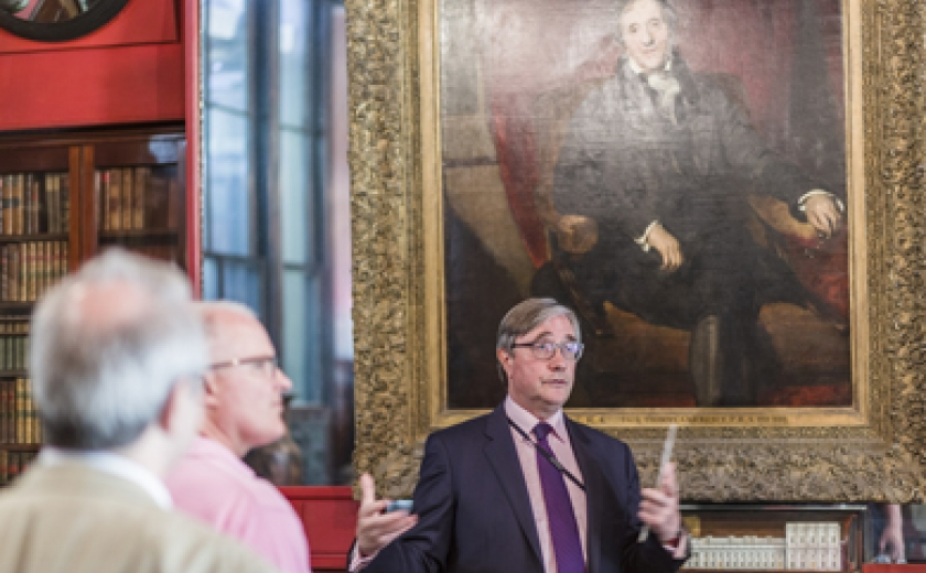 Photograph of a curator leading a tour, talking infront of the Lawrence portrait of Soane